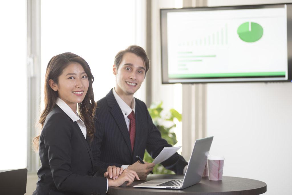 香港の証券会社で投資するメリットの男女会社員イメージ