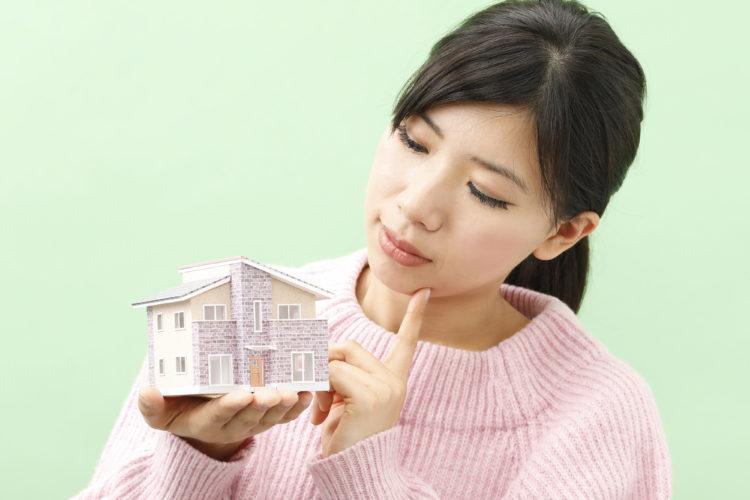 家を見つめる女性