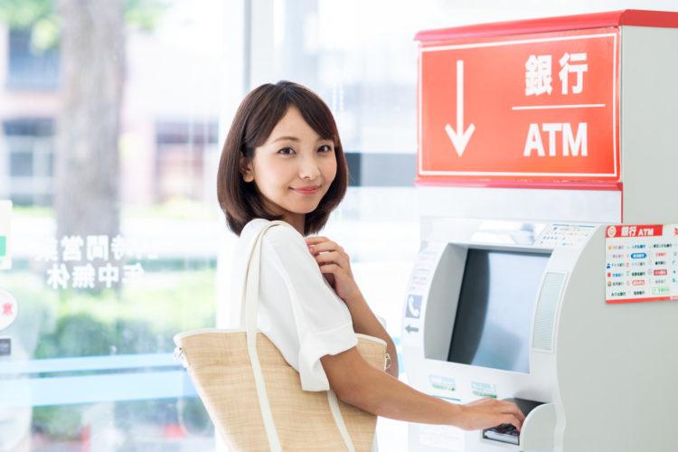 日本での引き出し手数料を確認してATM前で微笑む女性のイメージ