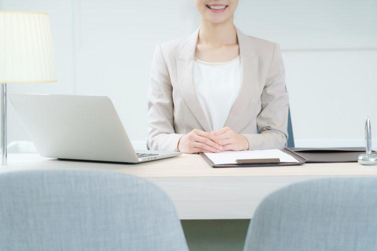 テーブルの向こうで微笑む窓口担当者