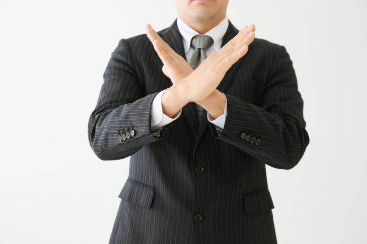 バツを腕で作る男性